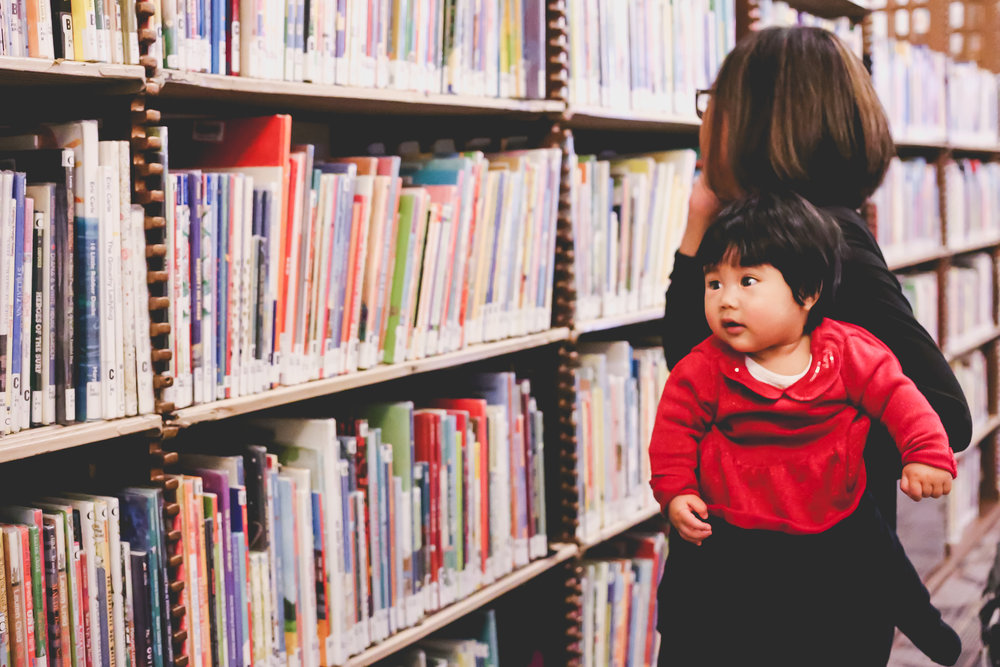 Baby looking at books with mom at the 42nd Street branch of the New York Public Library. Family Photography session with Jen Grima, Lehigh Valley Photographer.