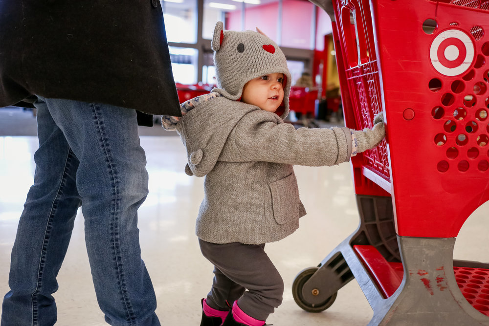 Toddler girl pushing the cart at Target during a documentary family photography session by Jen Grima of Lehigh Valley, PA.