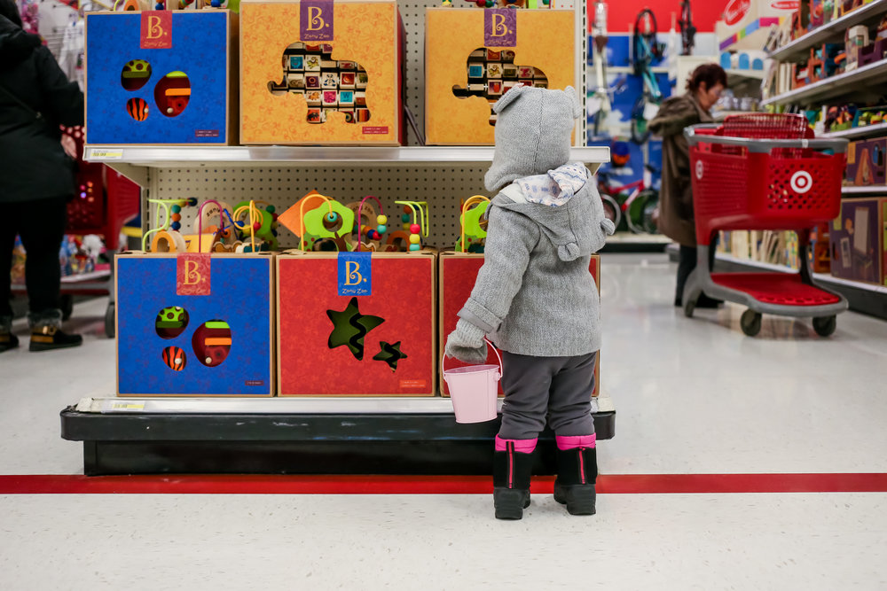 Two year old girl looking at toys in Target. Documentary family photography session, Emmaus, PA.