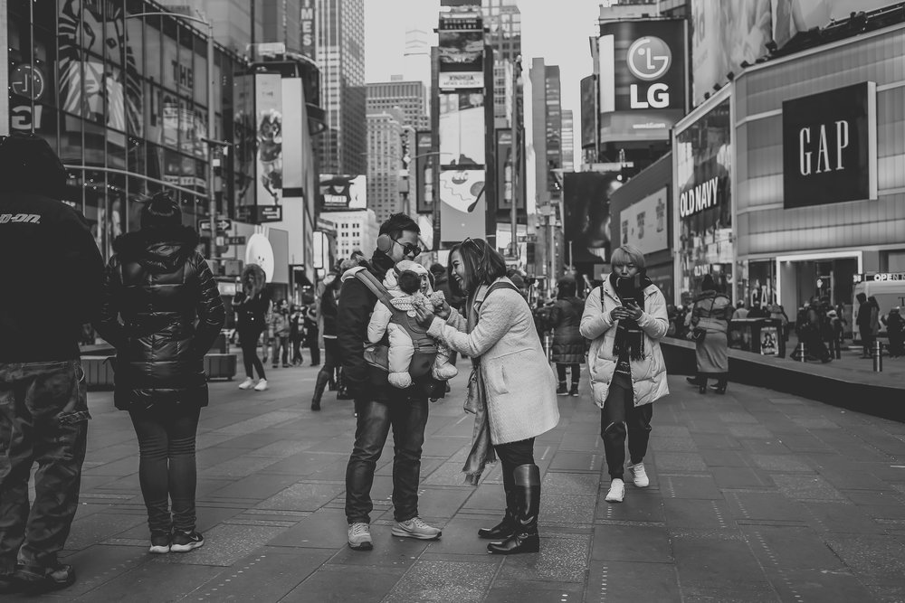 A mother tending to her baby in Times Square, New York City. Photo taken by Jen Grima, New York City vacation photographer.