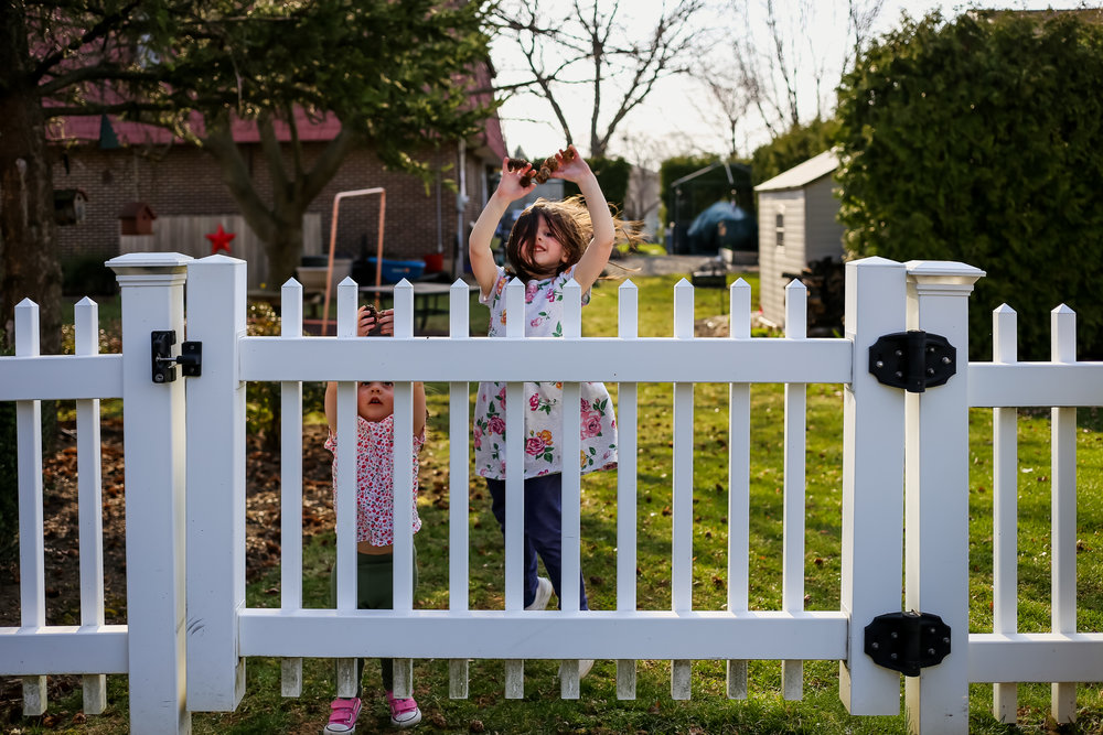 Little girls playing near behind a white picket fence in their backyard in Macungie, Pennsylvania.