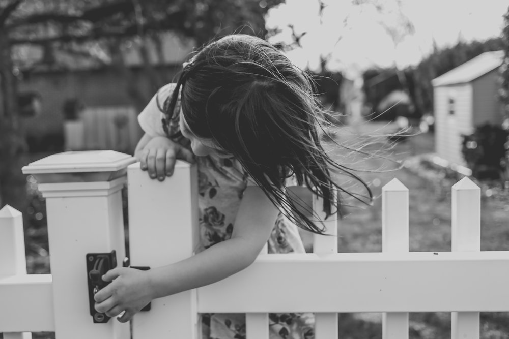 Girl trying to open the gate of a white picket fence on a warm spring day in Pennsylvania.