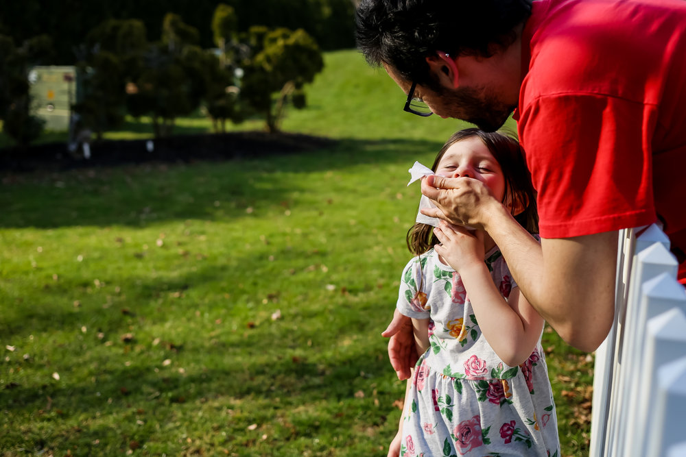 Father wiping his daughter's face while she plays outside in the backyard.