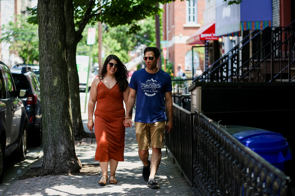 Engaged couple walking through Hoboken on a hot summer day.