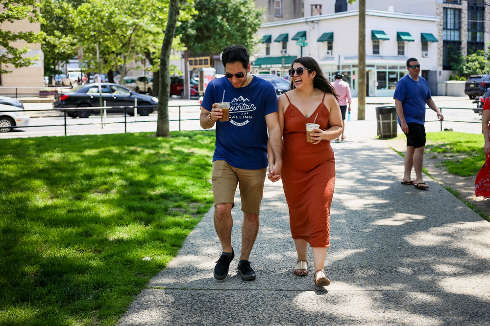 Walking through the park with iced coffee during their documentary style engagement photo session with Jen Grima, a Lehigh Valley photographer.