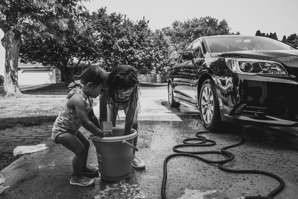 Girls washing the car during an outdoor at home summer session in Lehigh Valley, PA.