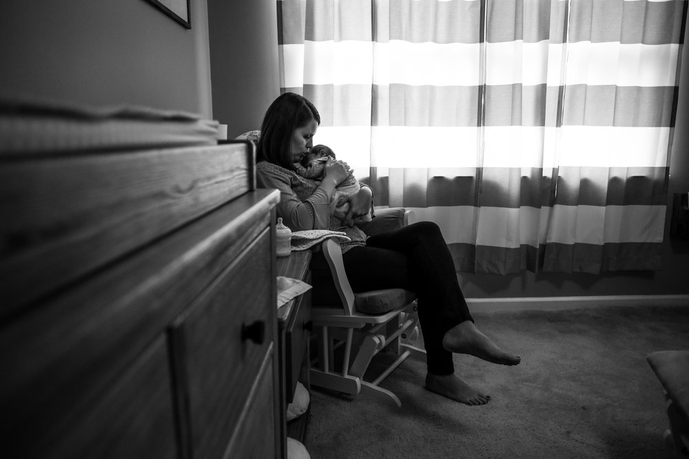 Mother and newborn daughter in their nursery rocking chair during an in-home newborn session in Lehigh Valley, PA.