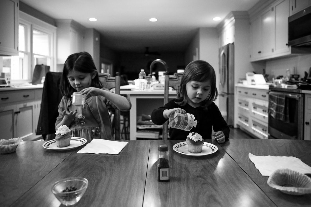 Children decorating their own cupcakes during an at home family photography session in Macungie, PA.