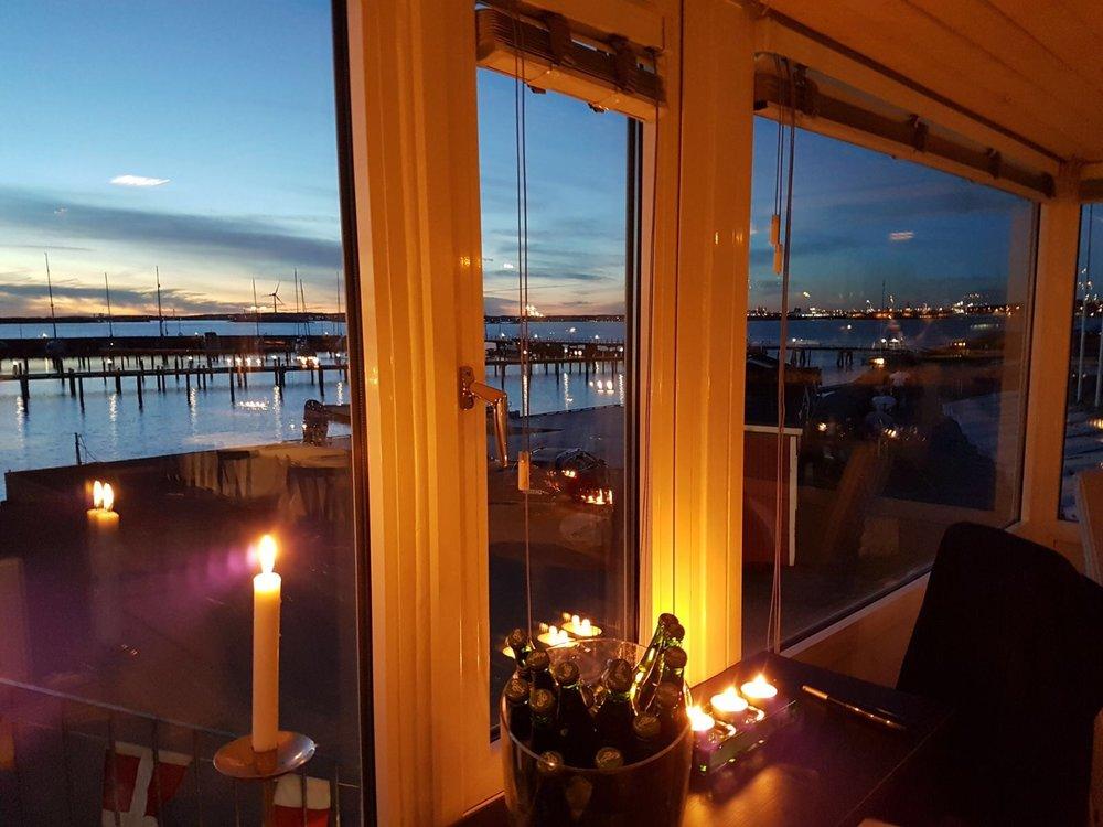 Levande ljus på bord med utsikt över Långedrags hamn.