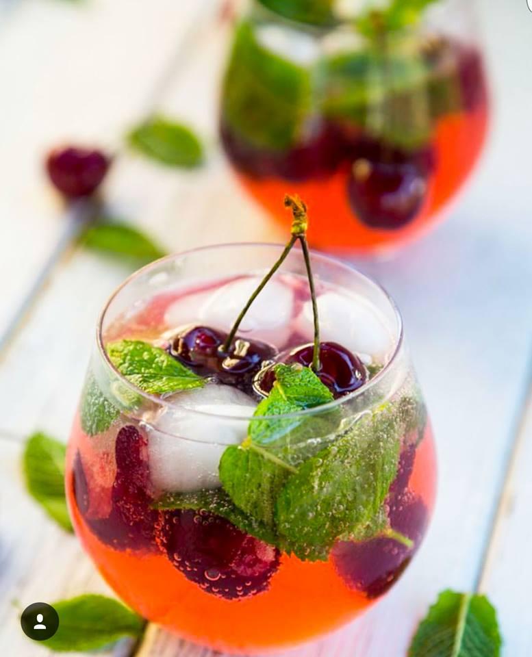 Röda drinkar med körsbär, mynta och is.