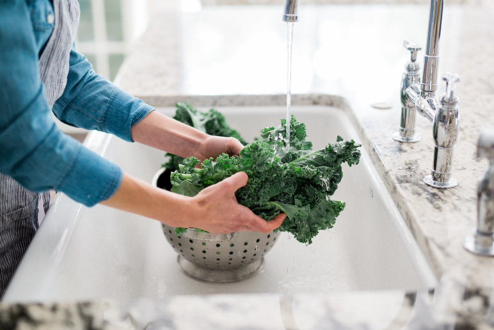 woman washing organic kale in stylish white kitchen