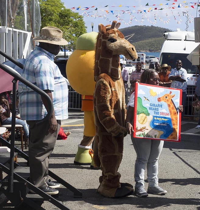 """Giraffe Hears the Drum  comes to life with this giraffe character who greeted and danced down the parade route, and came to pose with Governor Kenneth Mapp and say """"thank you"""" for supporting the Governor's Summer Reading Challenge program."""