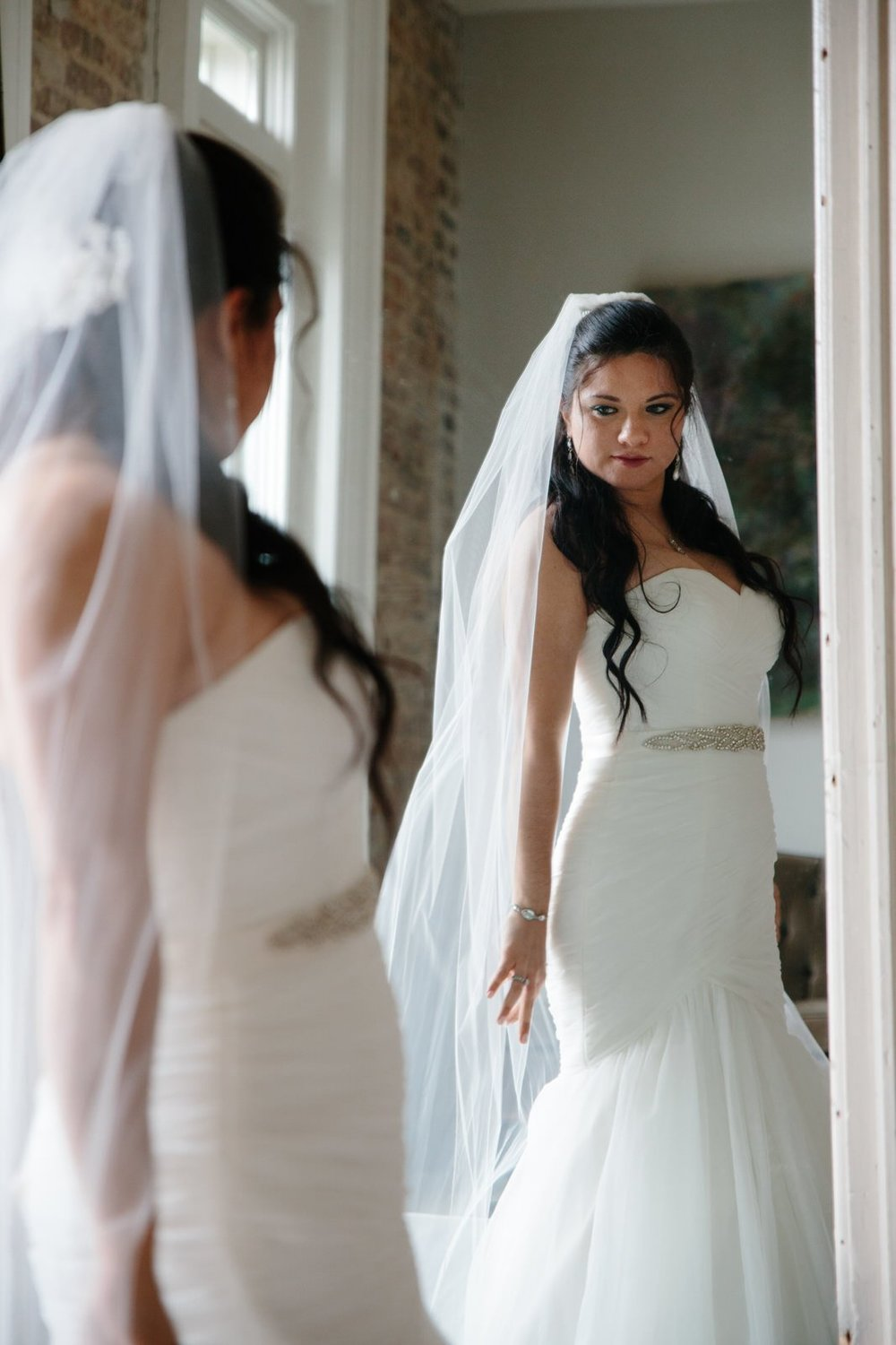 A beautiful bride admiring herself in the mirror
