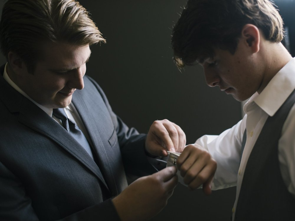 groom helping the brother get ready