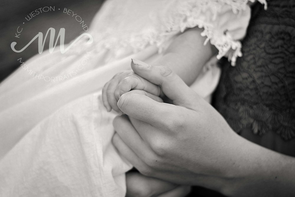 Black and white photo of mom holding baby's hand