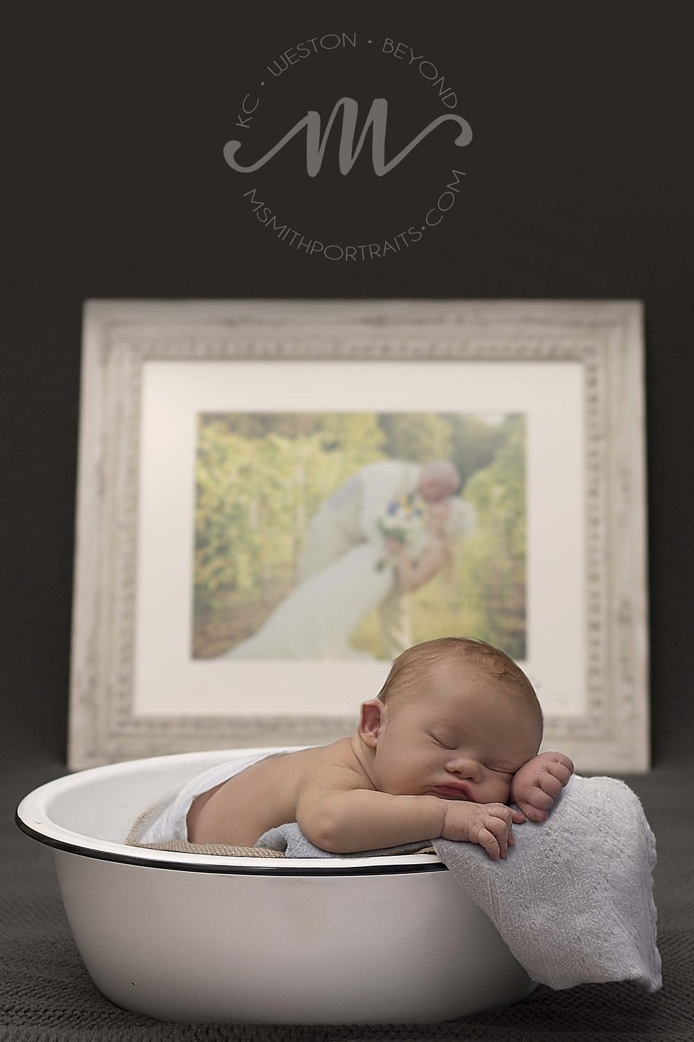 Newborn boy with parents' wedding photo