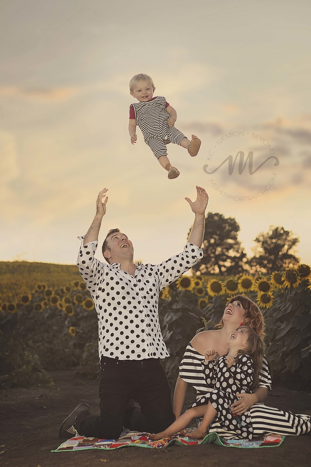 Photo of dad catching baby in sunflower field