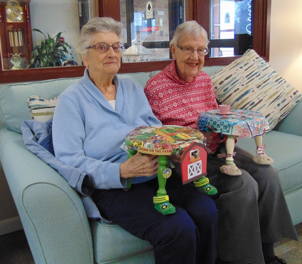 """These ladies are chuckling over """"Down on the Farm"""" and """"Peace by Piece,"""" two of the ambassador FootsieStools that visited their retirement community on a mission of mirth."""