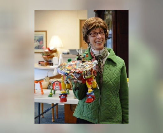 """Founder Valerie Gibbons laughs with residents of an assisted living facility over """"To Oz."""" Many people are inspired to share memories when they meet the FootsieStools. (Photo by facility staff)"""