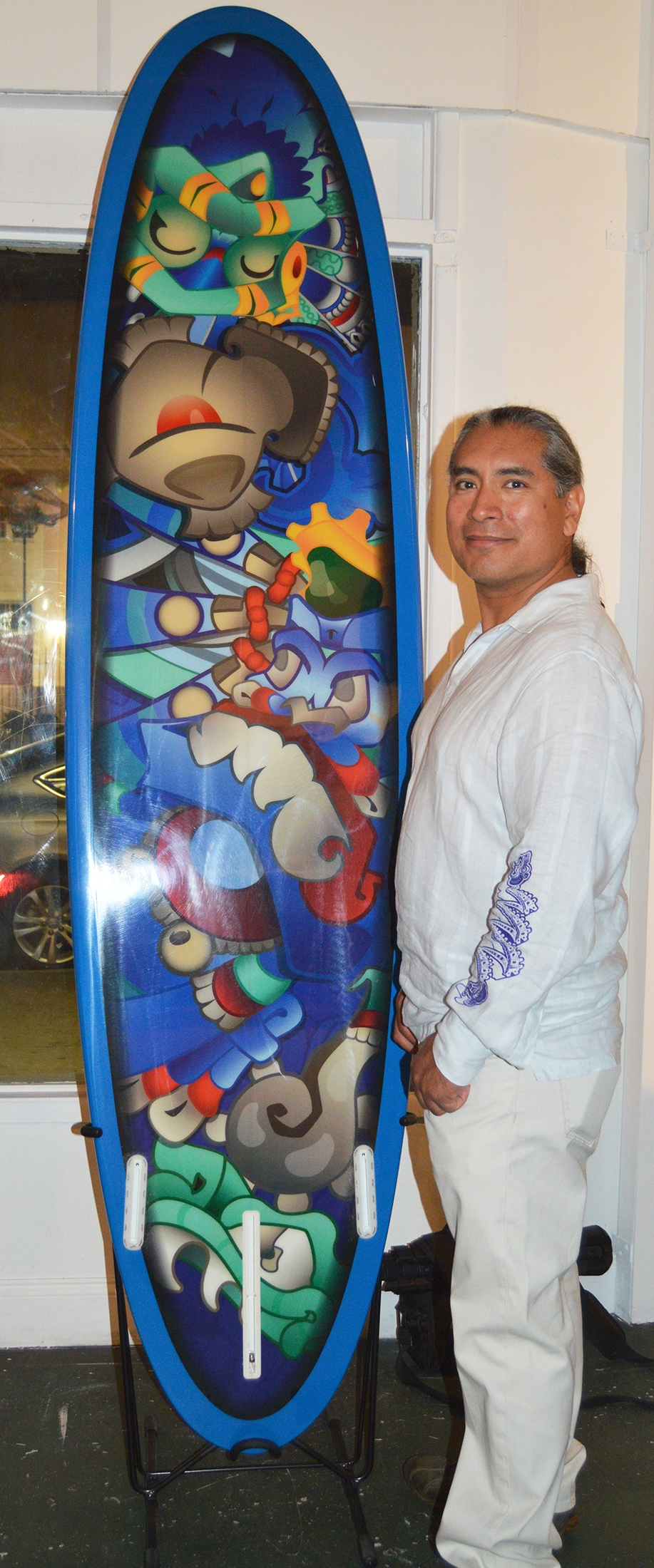 Angel Mendoza with his artful application on his one-of-a-kind surfboard.