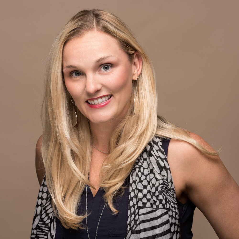 Professional business headshot of a woman in a studio setting.