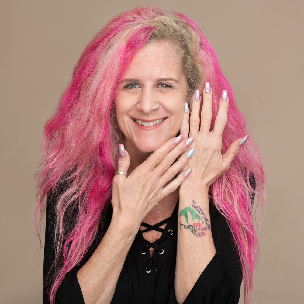 Smiling pink haired nail stylist displaying her colorful nails
