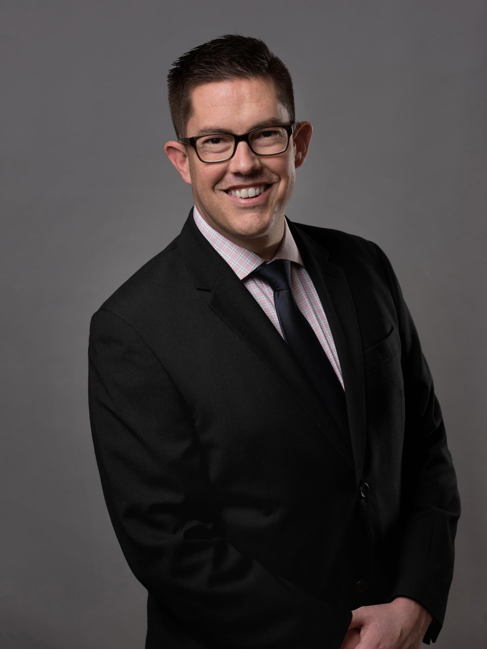 Smiling bespectacled man in a black business suit