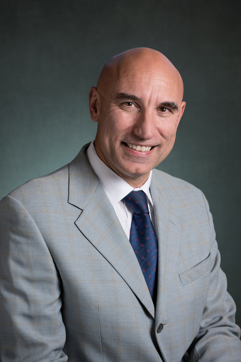 Smiling bald man wearing light gray business suit
