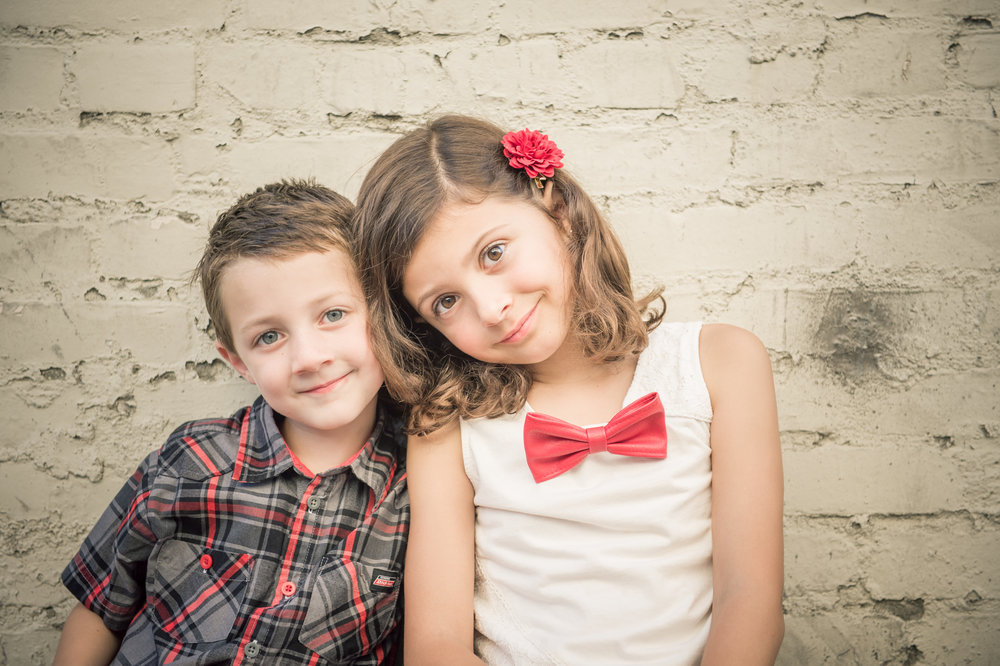 A boy and girl siblings sitting shoulder to shoulder