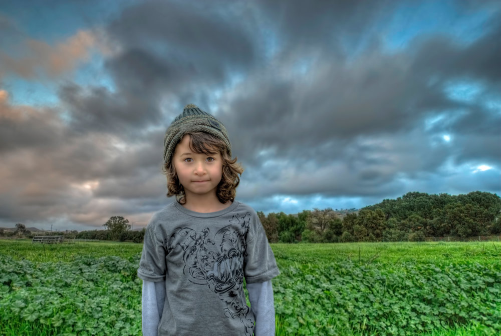 Long haired boy standing in front of a field of green under a dark clouded sky
