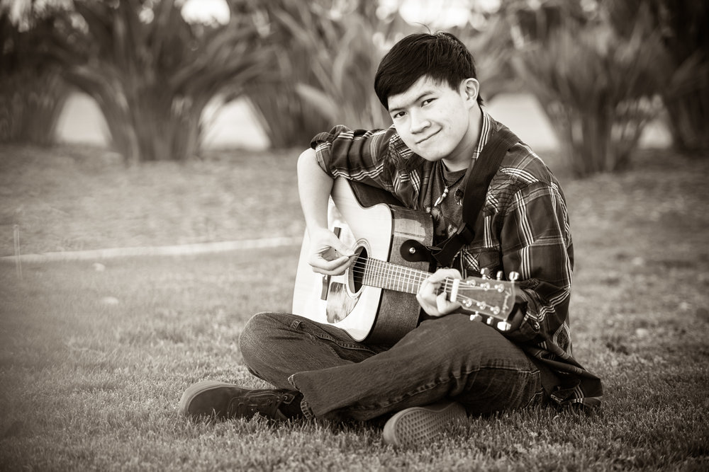 Black and white image of a senior boy playing an acoustic guitar