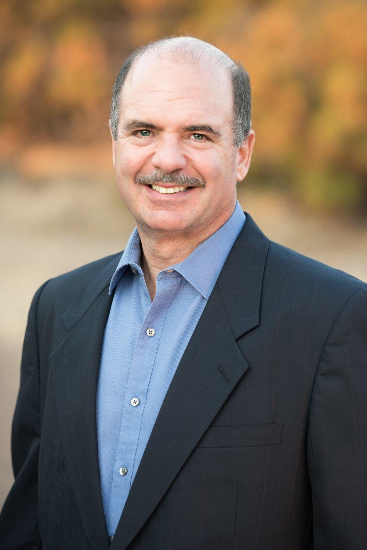 Smiling man wearing black business suit jacket
