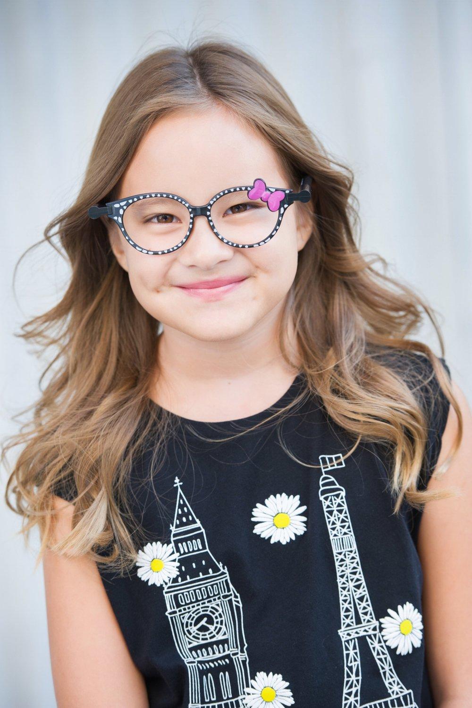 Smiling girl wearing prop glasses