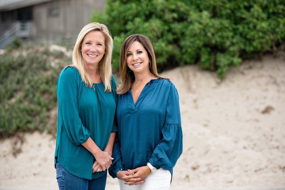 Two smiling women wearing blue blouses