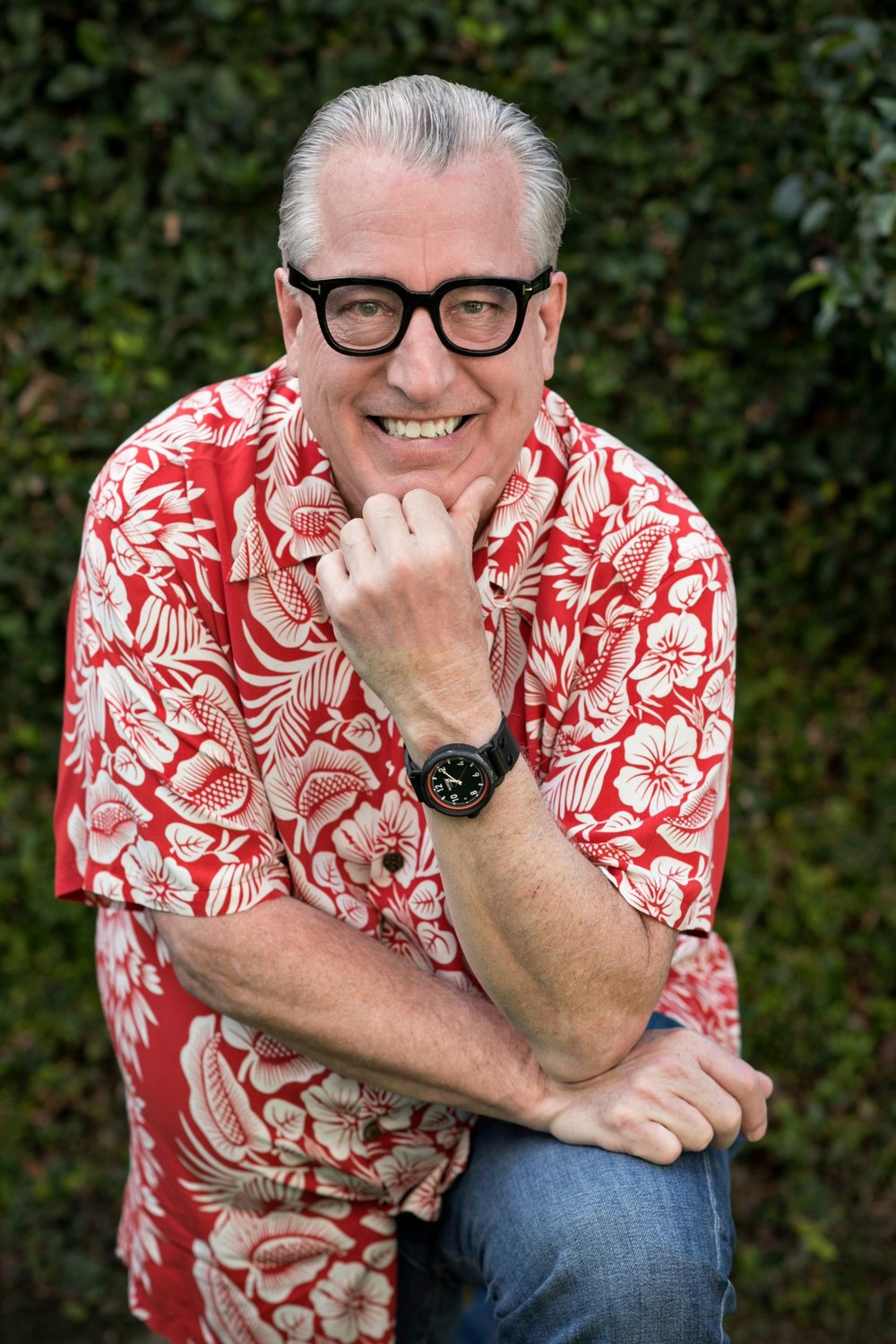 Smiling bespectacled man wearing a red hawaiian shirt