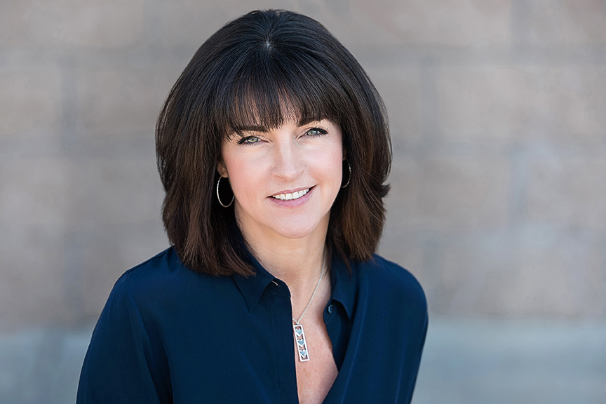 headshot of brunette woman with blue eyes wearing blazer for real estate headshot