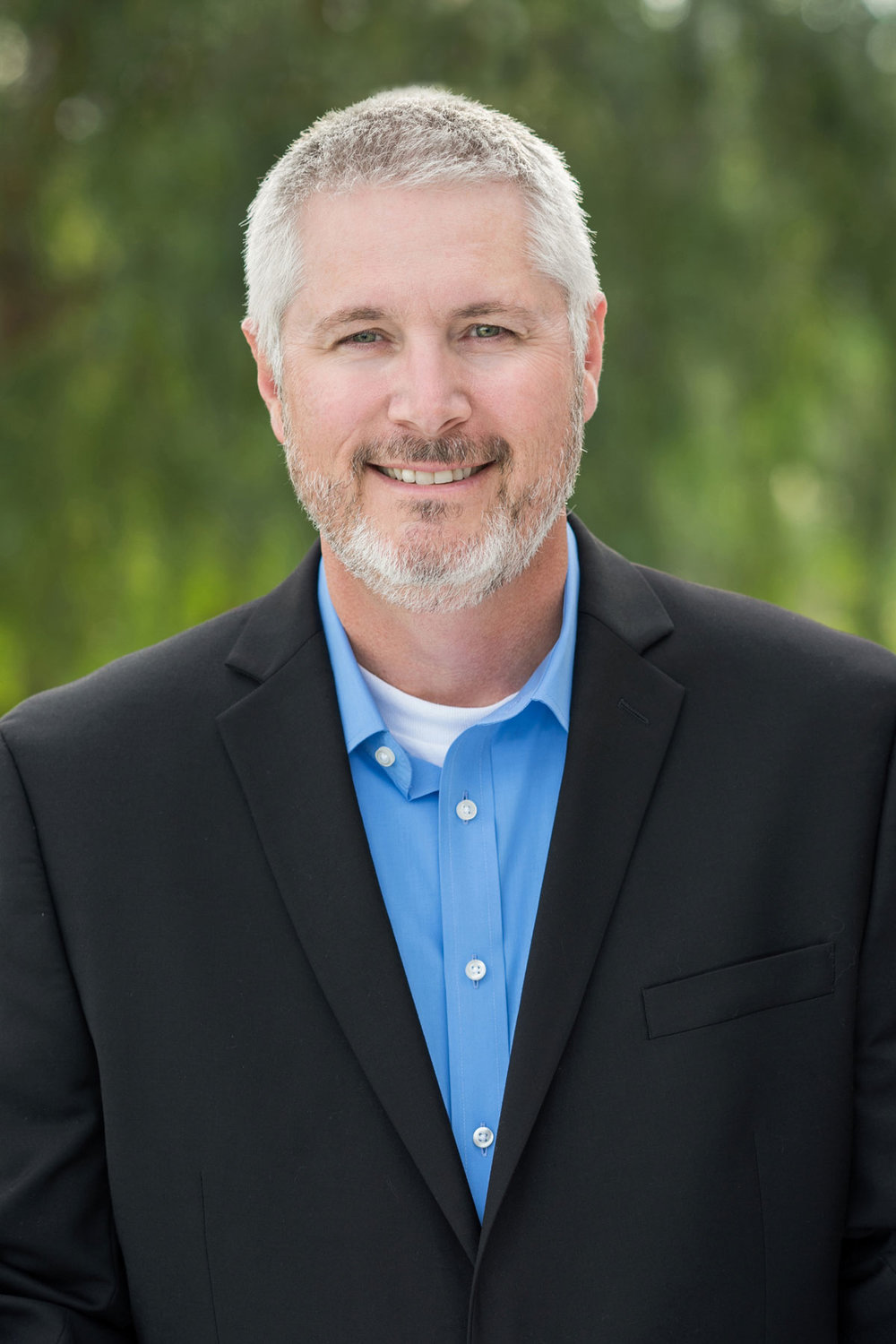 headshot of silver haired man wearing blue shirt and blazer outdoors