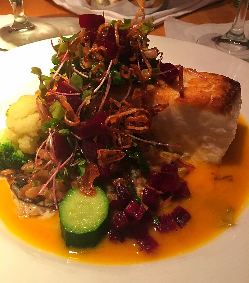 Pan seared halibut over mushroom risotto with seasonal veggies and beets, topped with crispy scallions.