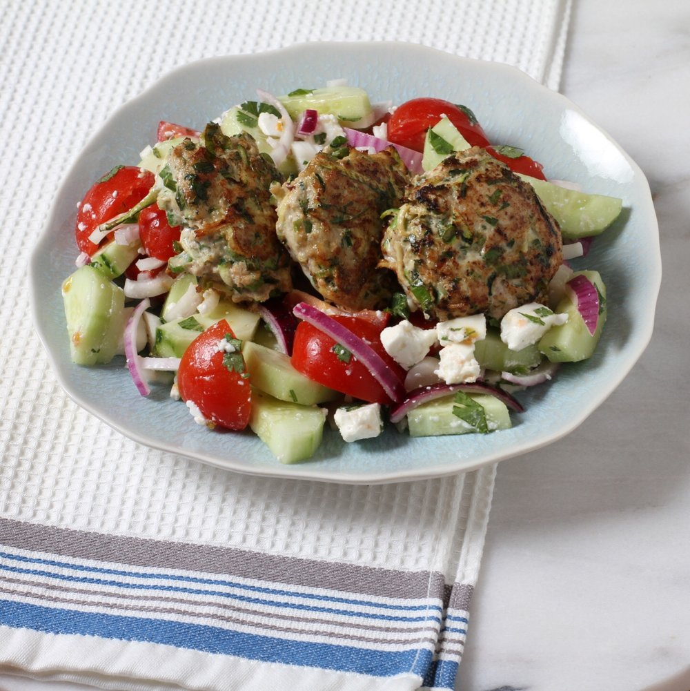 Turkey and zucchini burgers over a tomato and cucumber salad with feta. Yum.