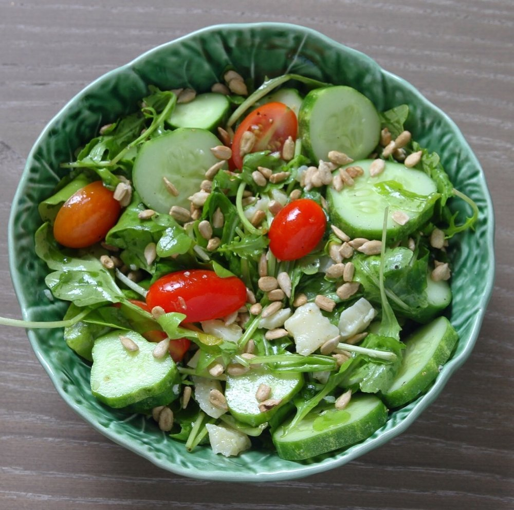 Arugula salad with fresh grape tomatoes, cucumbers, pine nuts, and Parmesan chunks.