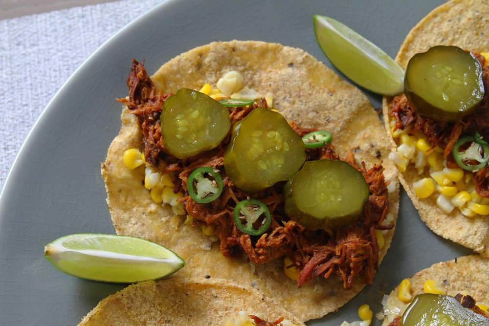 Slow cooker BBQ chicken tacos with homemade pickles, Serrano pepper, and corn.