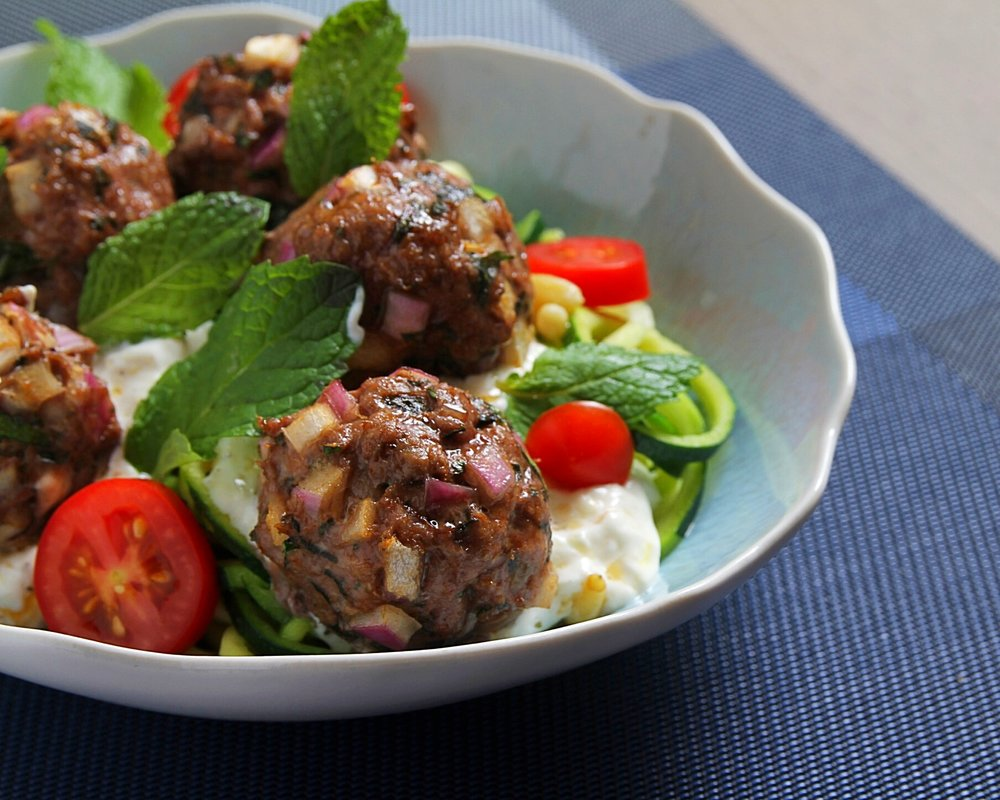 Greek lamb meatballs with zucchini noodles and lemon-yogurt dipping sauce. Fresh mint and grape tomatoes.