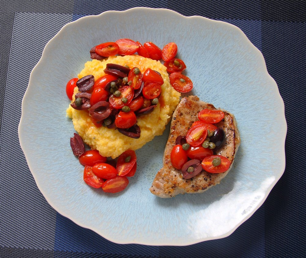 Pork chops and polenta topped with tomatoes, capers, and kalamata olives.
