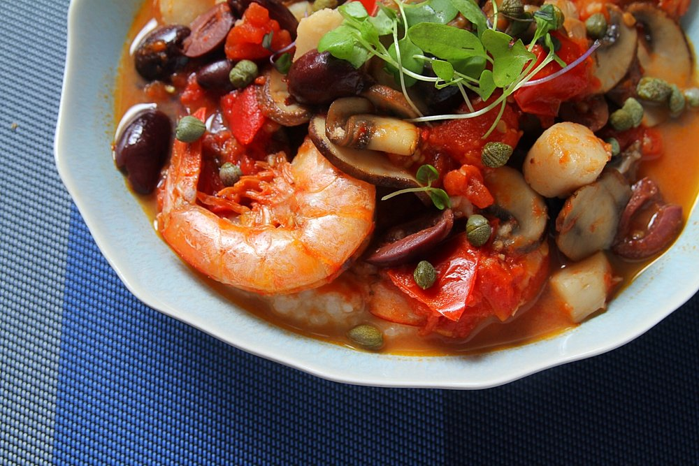 Seafood stew featuring homemade tomato sauce with shrimp and scallops. Served over Arborio rice.