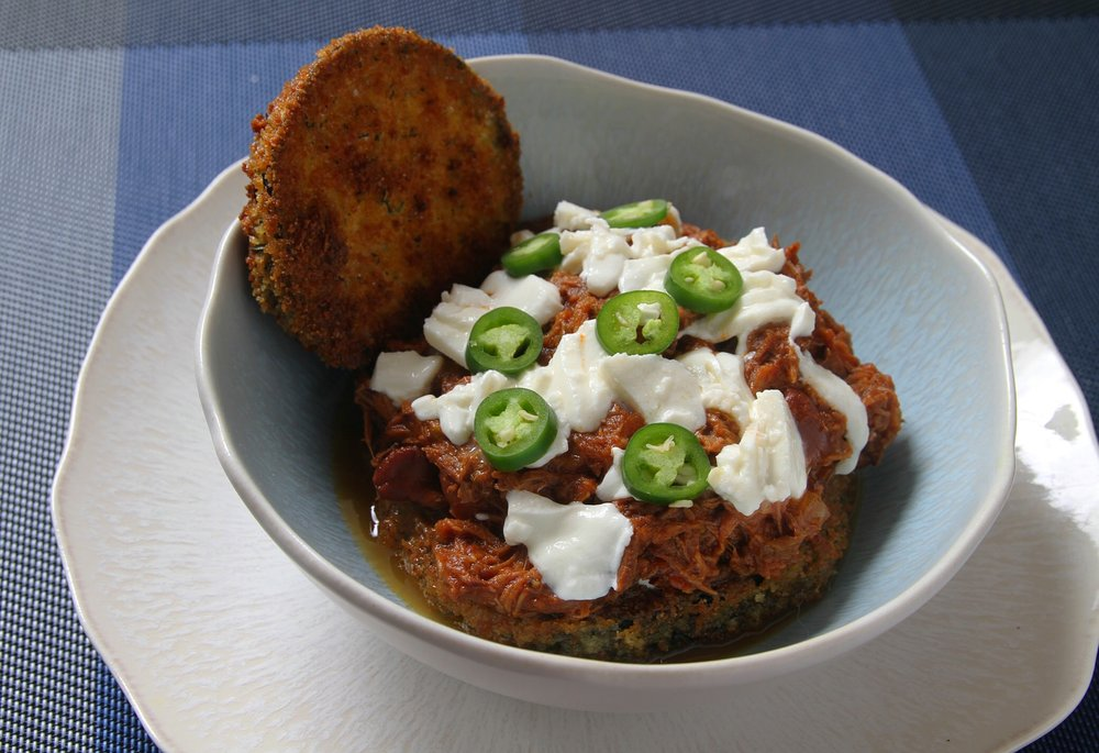Homemade slow cooker beef chili and crispy eggplant, topped with mozzarella and sliced Serrano peppers. Crispy eggplant disc garnish.