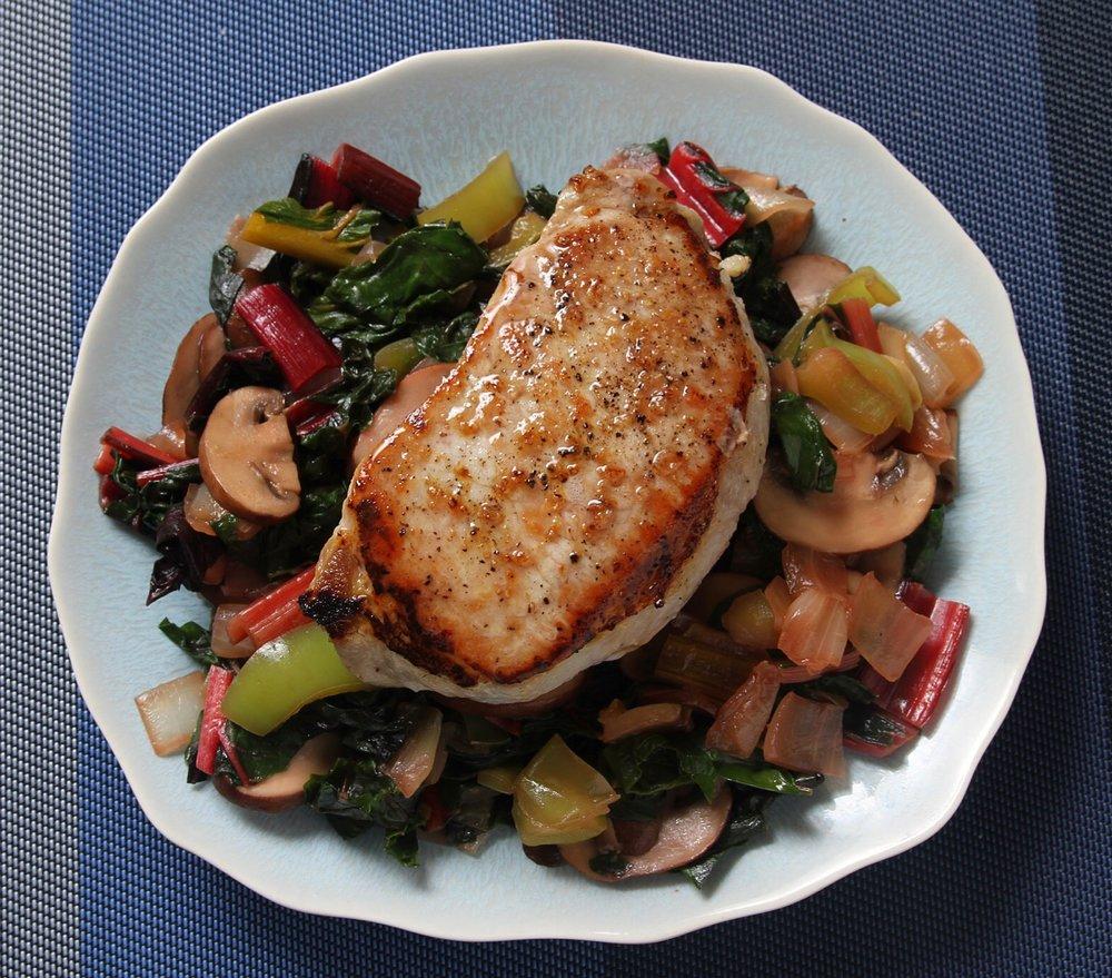 Boneless center cut pork chop over veggie medley of rainbow chard, mushrooms, onion, and pepper.