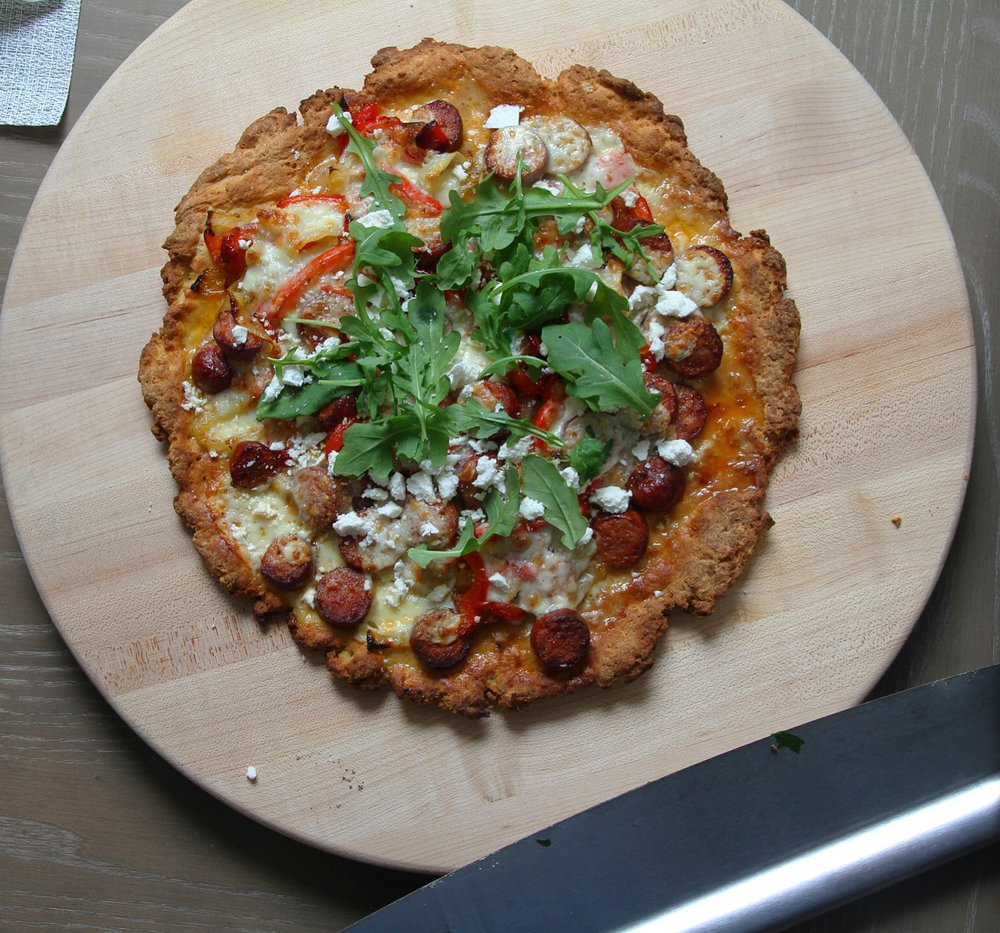 Bob's Red Mill Gluten Free pizza crust with roasted peppers and onion, andouille sausage, mozzarella, sprinkled ricotta salata, and fresh arugula.