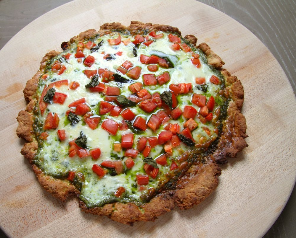 Basil pesto pizza with mozzarella and chopped tomatoes. Forgot to top it with fresh basil! Bob's Red Mill crust.