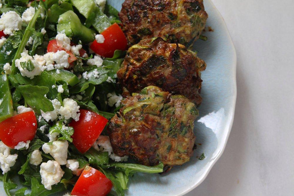 Lamb and zucchini burgers with arugula salad.