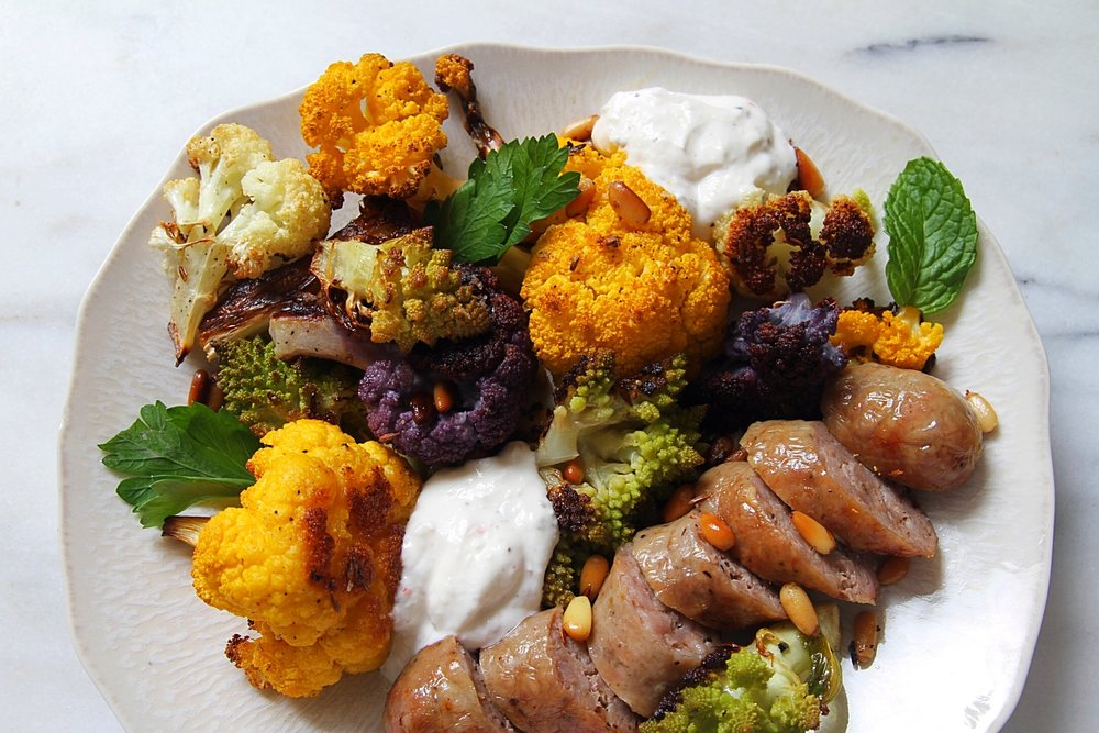 Roasted sausages and cauliflower with cumin seeds and pine nuts.